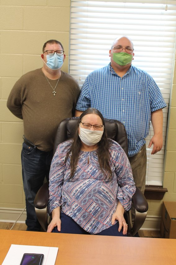 Clients Bea Smith, seated, Chris Racine, left, and Tony Madaris at the ARC office in Loxley.