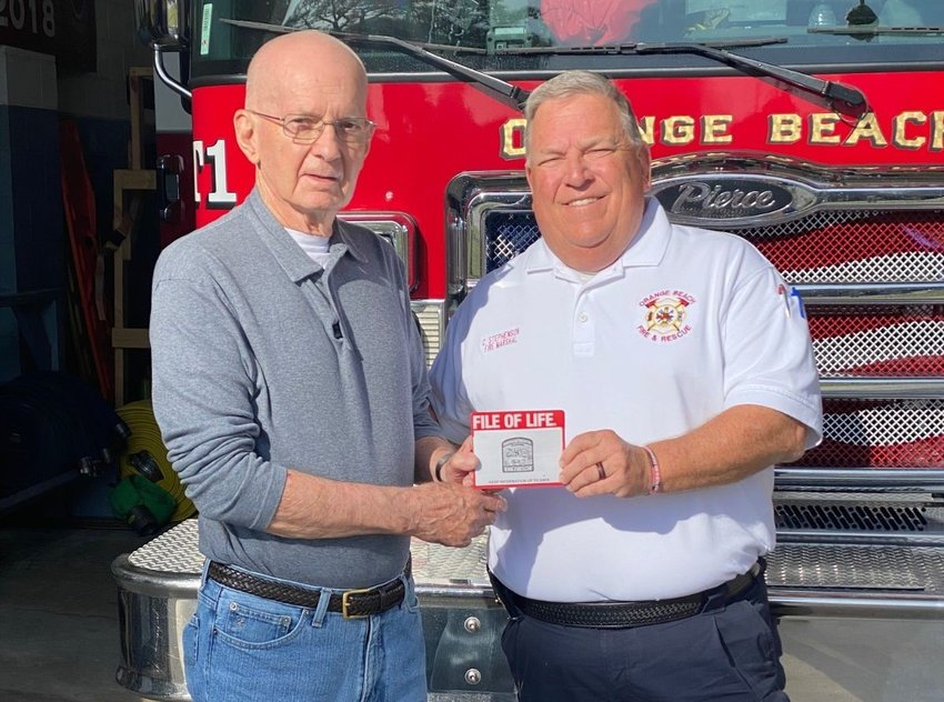 Orange Beach's Fire Marshal Craig Stephenson hands resident Lionel Epp a File of Life packet. As part of the program, the Orange Beach Fire Rescue is providing packets to senior citizens and citizens with chronic medical problems living in the City of Orange Beach.