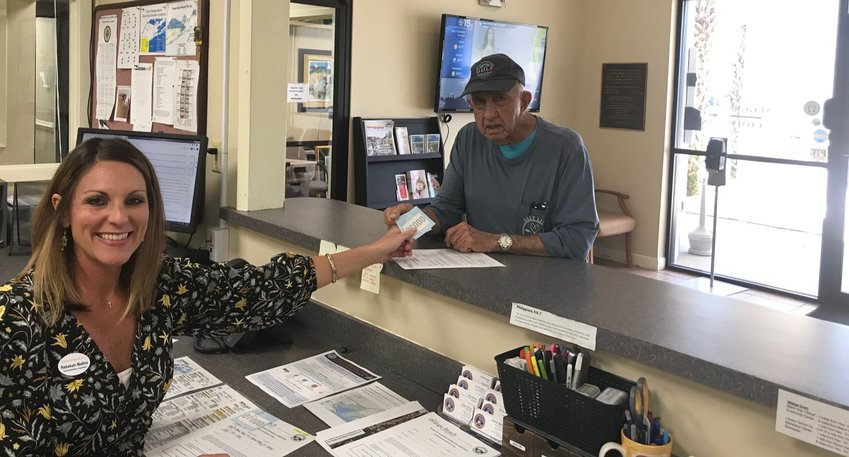 Allen McElroy picks up two Orange Beach Resident parking passes at City Hall.
