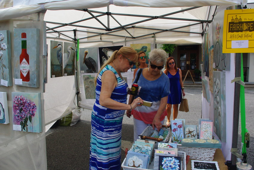 Visitors to the Fairhope Arts and Crafts Festival look over paintings by Daphne artist Linda Scott.