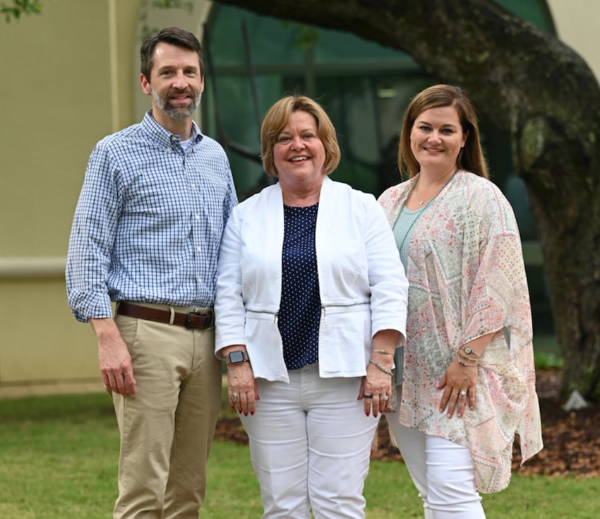 Sheila Hodges, center, announced she has transferred ownership of Gulf Shores, Ala.- based Meyer Vacation Rentals to CEO Les Williams, left and President Michelle Hodges, right.