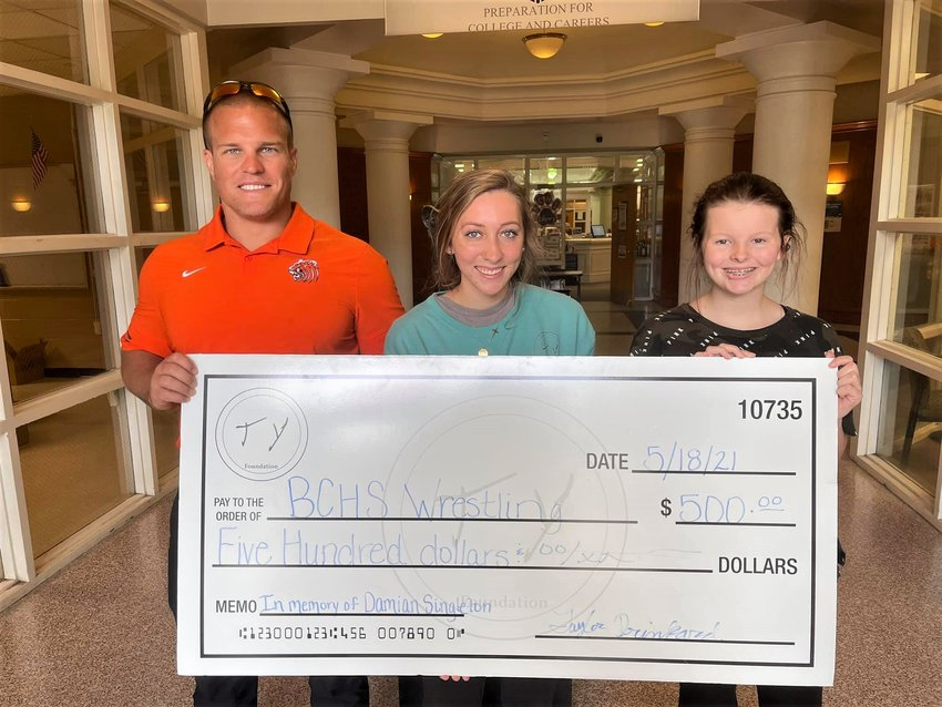 Ty's sister Tayler Drinkard, center, presented the check to Miranda Singleton, Damian's sister, and Joiner Stewart, Baldwin County High School's wrestling coach.