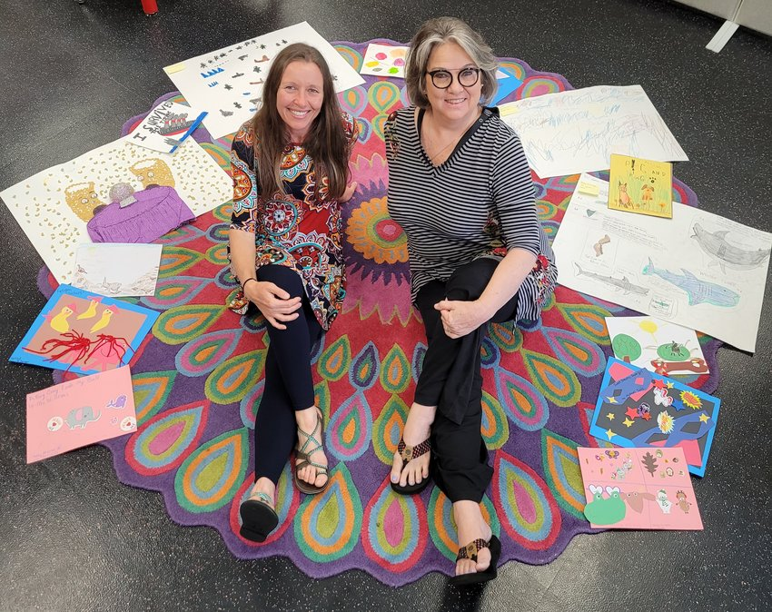"""Anna Hallex and Kelley Wansley, of the Children's Department at the Library, surrounded by April's """"Read A Book"""" project entries."""
