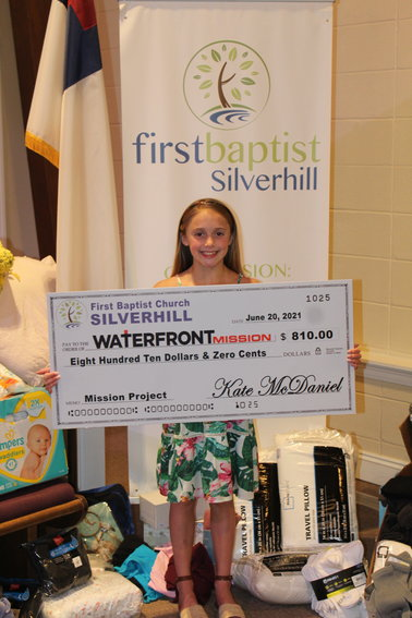 Kate McDaniel recently presented a check for $810 to the Waterfront Mission in Foley.