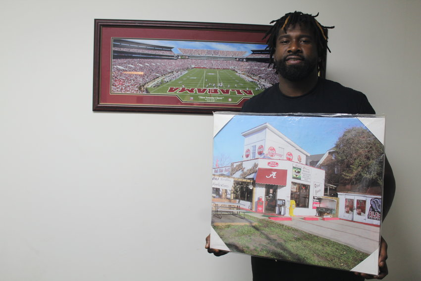 Former Alabama and NFL standout Wallace Gilberry holds a poster of Rama Jama's in Tuscaloosa, a landmark that was the inspiration for his restaurant Berry's Bistro in his hometown of Bay Minette.