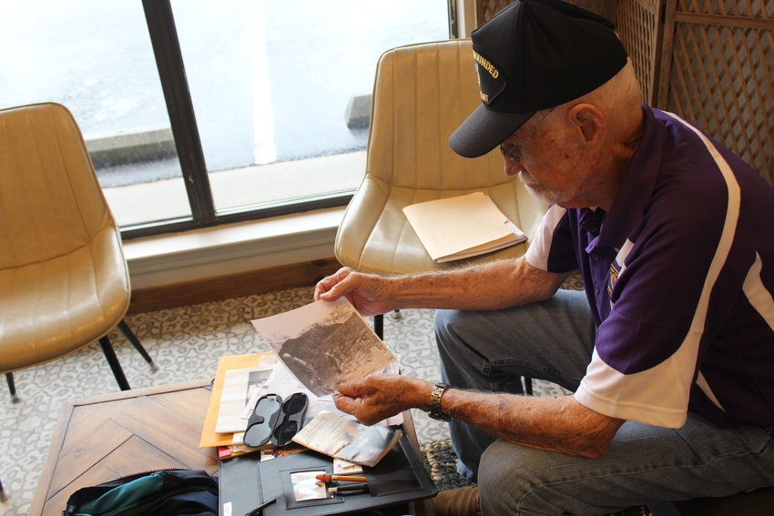 Silverhill resident Ed Evans looks over photos from his time in Korea and his invitation to represent the state of Alabama in the 2021 Purple Heart Patriot Project Sept. 27-30 in New York.