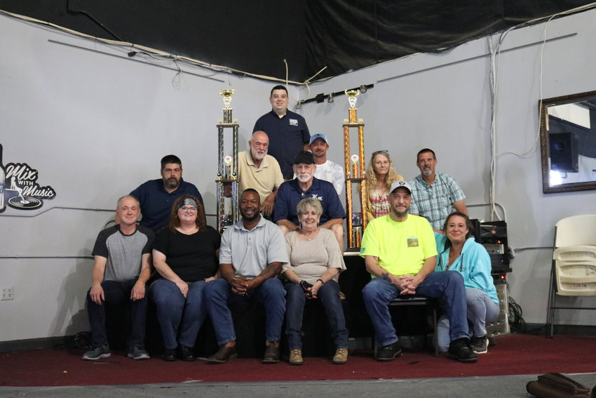 """The 8-Ball team """"Chalk Is Cheap"""" and the 9-Ball team """"Family Traditions"""" with their qualifying trophies.  Top row: Russell Holt, APA League Operator.  Middle row, from left: Daniel Owens, Dick Craig, Jon Traudt, Josh McCormick, Janice Thomas and Louis Ewing Jr.  Bottom row, from left: Tim Gier, Christina Mason, Frank Mason, Donna Westmoreland, Gary Slaughter and Michelle Szidon-Ewing.  Not present: Amanda Ewing, Ricky """"Allen"""" Moss, Cody Wible and Andy Schnider."""