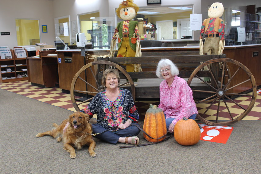 Robertsdale Library Director Cynthia Nall, assistant Liz Silcox and resident canine Gracie May get ready for Halloween Fun Night Thursday, Oct. 21 at the Library.