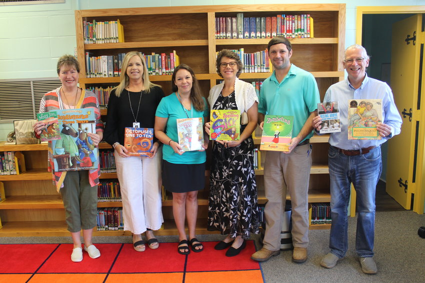 The Robertsdale Rotary Club and Dickerson Literacy Initiatives came together to make a donation of 65 books recently to Elsanor School library media specialist Susan Loy and Principal Charlotte Gray. The donation represents about half of the 125 books donated so far to the school which is looking to replace a total of 4,000 books. Pictured, from left, are Kimberly Knoth with Dickerson Literacy Initiatives, Gray, Loy, Robertsdale Rotary Club President Rebecca Mills, Rotary Club Vice President/President Elect Ryan Frolik and Carl Dickerson.