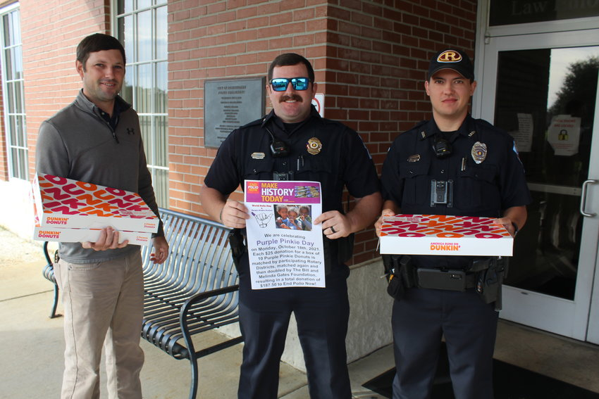 Ryan Frolik, left, Robertsdale Rotary Club vice president/president-elect for 2021-22, delivers Purple Pinkie donuts to the Robertsdale Police Department on Monday, Oct. 18 as part of Purple Pinkie Day for Polio Plus Eradication. Pictured with Frolik are RPD officers Fred Stringer, center, and Zach Williams.