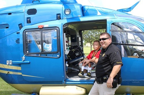 Shining Star Camp director Cpl. Jeff Spaller shares a moment with 5-year-old Colin Dodd of Foley aboard an Air Methods (Baptist Hospital) Life Flight helicopter July 20 at Central Baldwin Middle School.