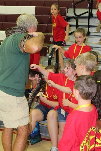 Wes Moore of Alligator Alley in Summerdale is always a hit at the Shining Star Camps, showing off a boa constrictor at the camp in Robertsdale.