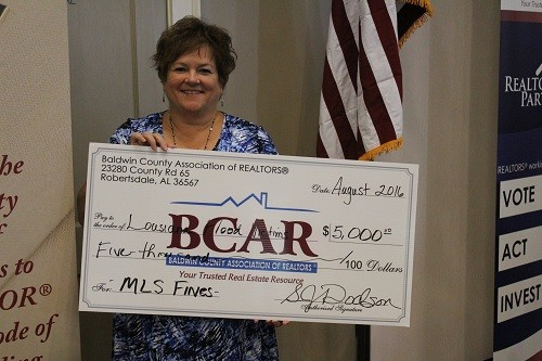 BCAR Chief Executive Officer Sheila Dodson with a display representing a $5,000 check that the association is donating to flood victims in Louisiana. BCAR is also accepting supply donations for flood victims at its central office in Robertsdale.