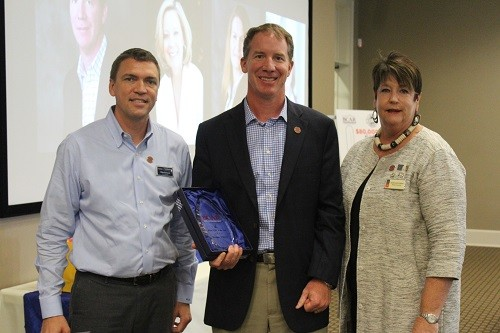 2016 Realtor of the Year Morgan Ashurst receives his award from 2015 BCAR Realtor of the Year Mike Steward and 2016 Board President Mary Jane Owen.