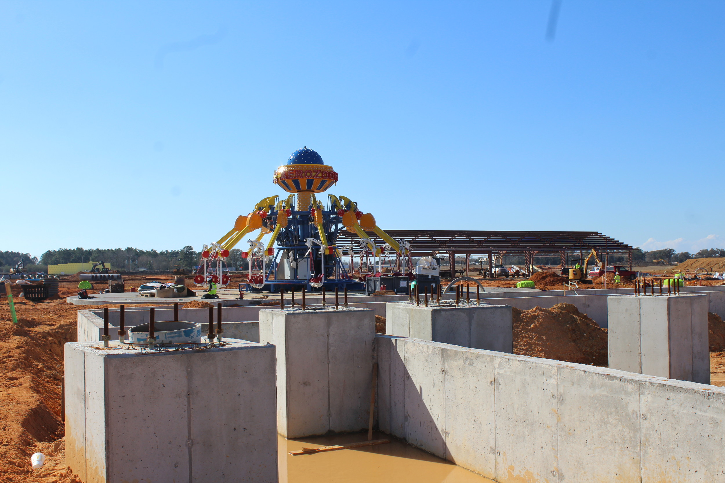 Inside theme park, facing west. The concrete slabs are the foundation for the roller coaster. The steel-framed building is the maintenance building for the park.