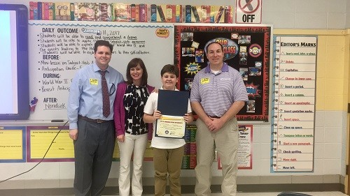 WALA Fox 10 TV's meteorologist Michael White, Gulf Shores Middle School faculty member Carly Nelson and Baldwin EMC Energy Marketing Specialist Brad Taylor congratulate Gulf Shores Middle School student Fisher Bryant on his Shining Star Student award.