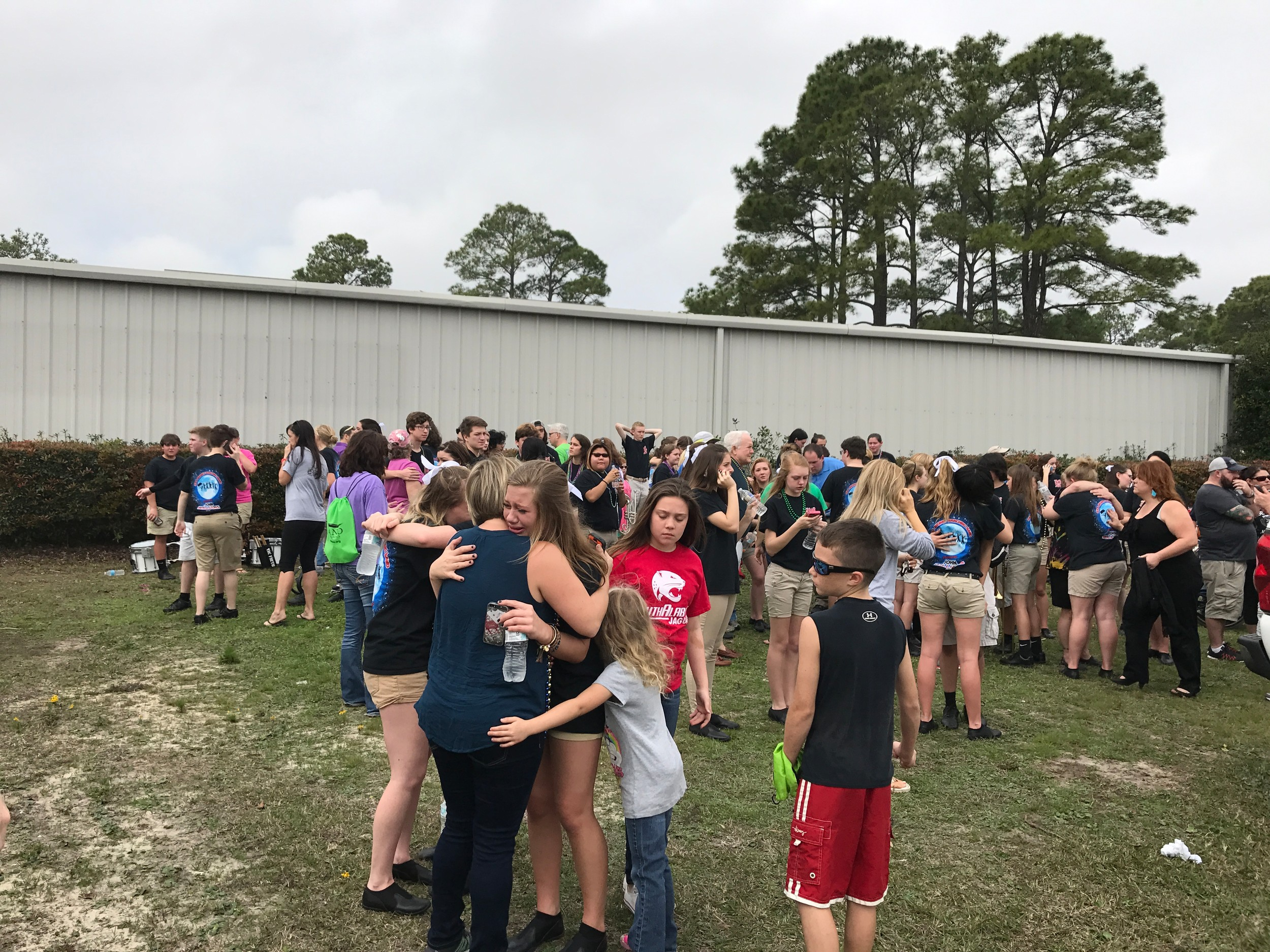 Students in the Gulf Shores High School Band console one another after a car accident in the city's Mardi Gras Parade injured twelve of the band's members.