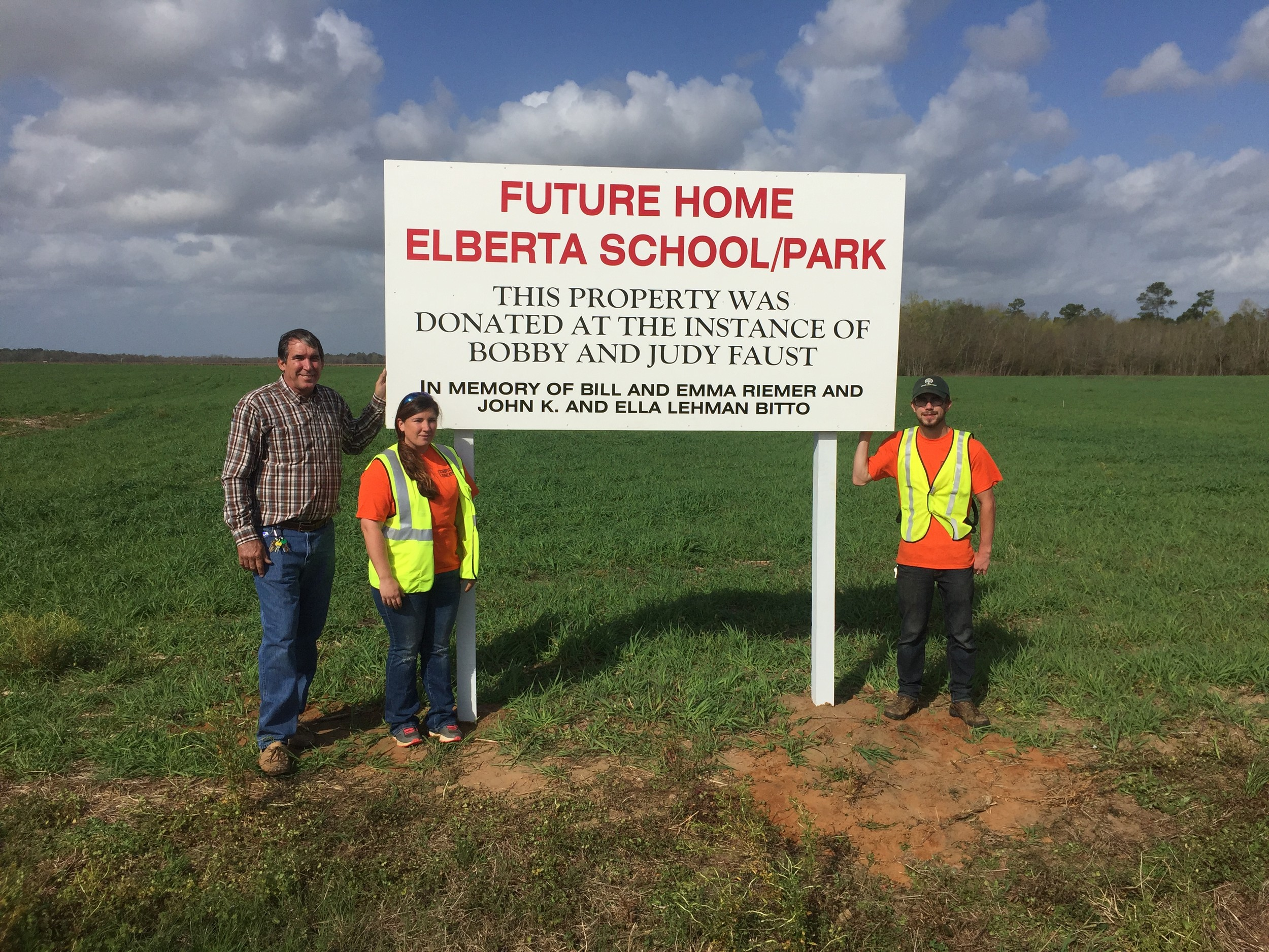 Mayor Jim Hamby and city staff stand with the newly erected sign thanking the Faust family for their 38 acre land donation to the town of Elberta.