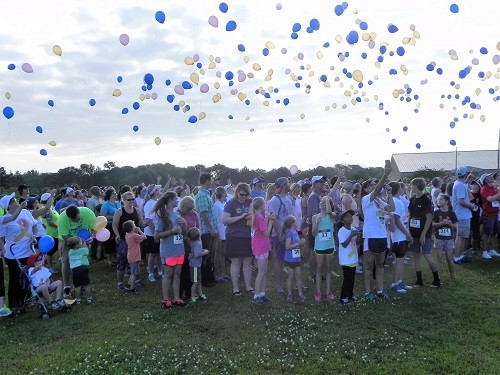 Participants in the Tenley Tough 5K release balloons before the race in honor of then-cancer patient Tenley Norman. Now nearing her second birthday, Tenley is cancer free and the event raised over $12,000 toward her medical bills.
