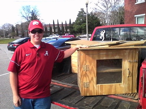"Evan White with one of the ""Free Little Libraries"" he built for an Eagle Scout project."