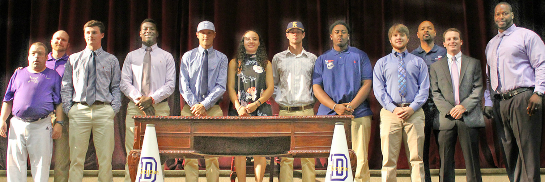 Daphne High collegiate-signing athletes with team manager Joey Wolfe, coaches Owen Davis (Baseball), Cedric Yelding (Boys Basketball), Mason Dunn  (Girls Basketball) and athletic director/ football head coach Kenny King.
