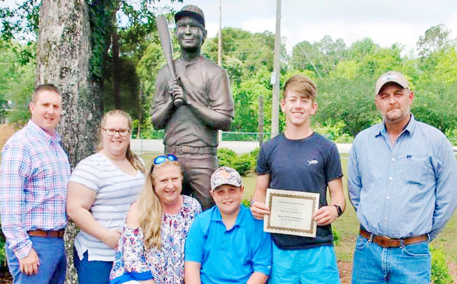 Mikey DeFee Memorial Scholarship Award recipient Drew Parker at Mikey's memorial statue at Halliday Park in Bay Minette.