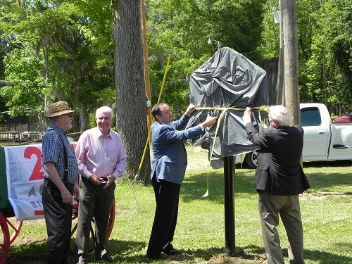 Baldwin County Commissioners Chris Elliott and Frank Burt unveil the Mims Ferry and Holley Creek/Montgomery Hill Landing historic marker.