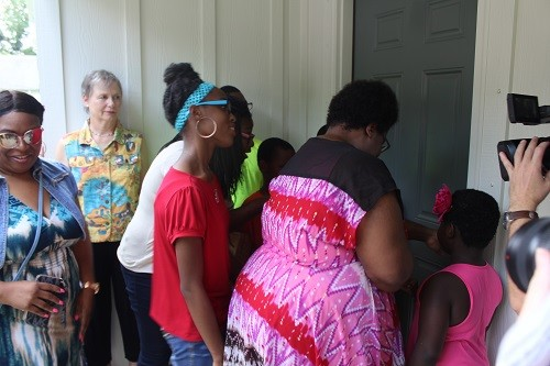 Kassie Betts opens the door to her new home in Bay Minette following a celebration and blessing ceremony Wednesday, July 26 with Habitat for Humanity of Baldwin County.
