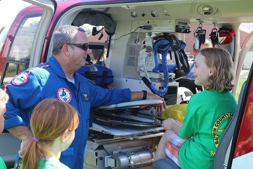 Medstar Flight Paramedic Nicky Fortune shows a camper the close confines of an emergency response helicopter during the Baldwin County Sheriff's Office Shining Star Camp at Central Baldwin Middle School Wednesday.