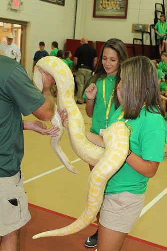 Volunteers Kayleigh Tolbert and Abbie Vaughn hold albino boa constrictor One-Eyed Willie.