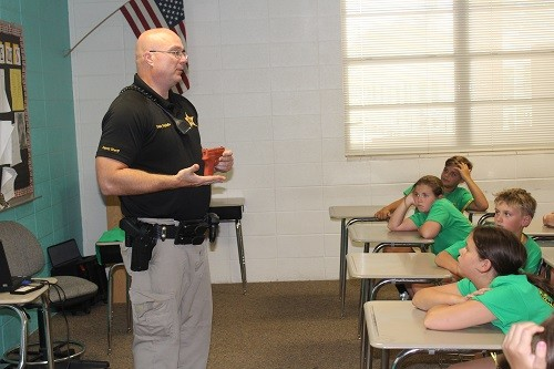 School resource officer, BCSO Deputy Craig Stoffle shows campers a tool used in weapons training during a firearms safety talk.
