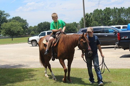 A junior deputy with the BCSO's Mounted Posse gives a camper a ride during Shining Star Camp last week at CBMS.