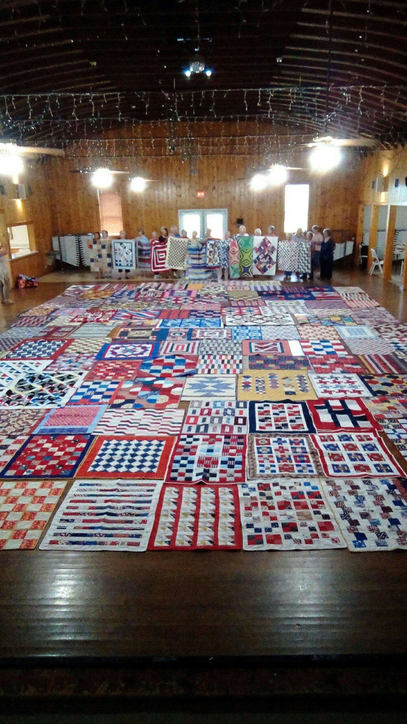 Quilts donated to veterans at the William F. Green Veterans Home in Bay Minette cover the floor, including several held by Stitch-N-Friends members, at the PZK Hall in Robertsdale. The quilts were delivered at the end of June for the veterans to have by the Fourth of July.