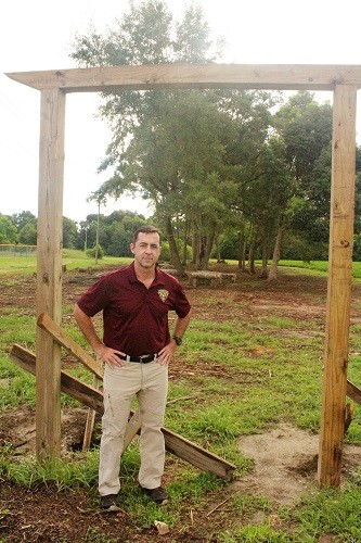 "Robertsdale High School JROTC Commander Lt. Col. Scott Meehan stands at the entrance to the school's planned ""confidence"" course, which has been dubbed Davy Jones's Locker."
