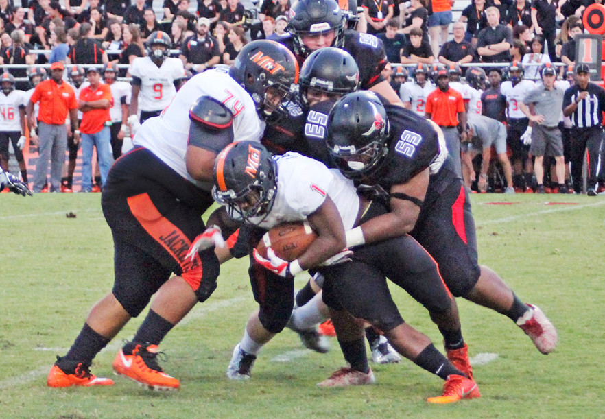 Monjai Cooks (53) and teammates tackle McT's Bryan Hill at SFHS.