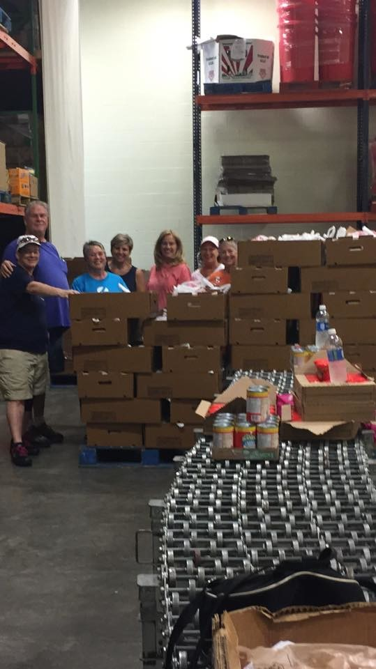 A group of volunteers pack backpacks for children in our community at Feeding the Gulf Coast's main branch in Theodore, AL.