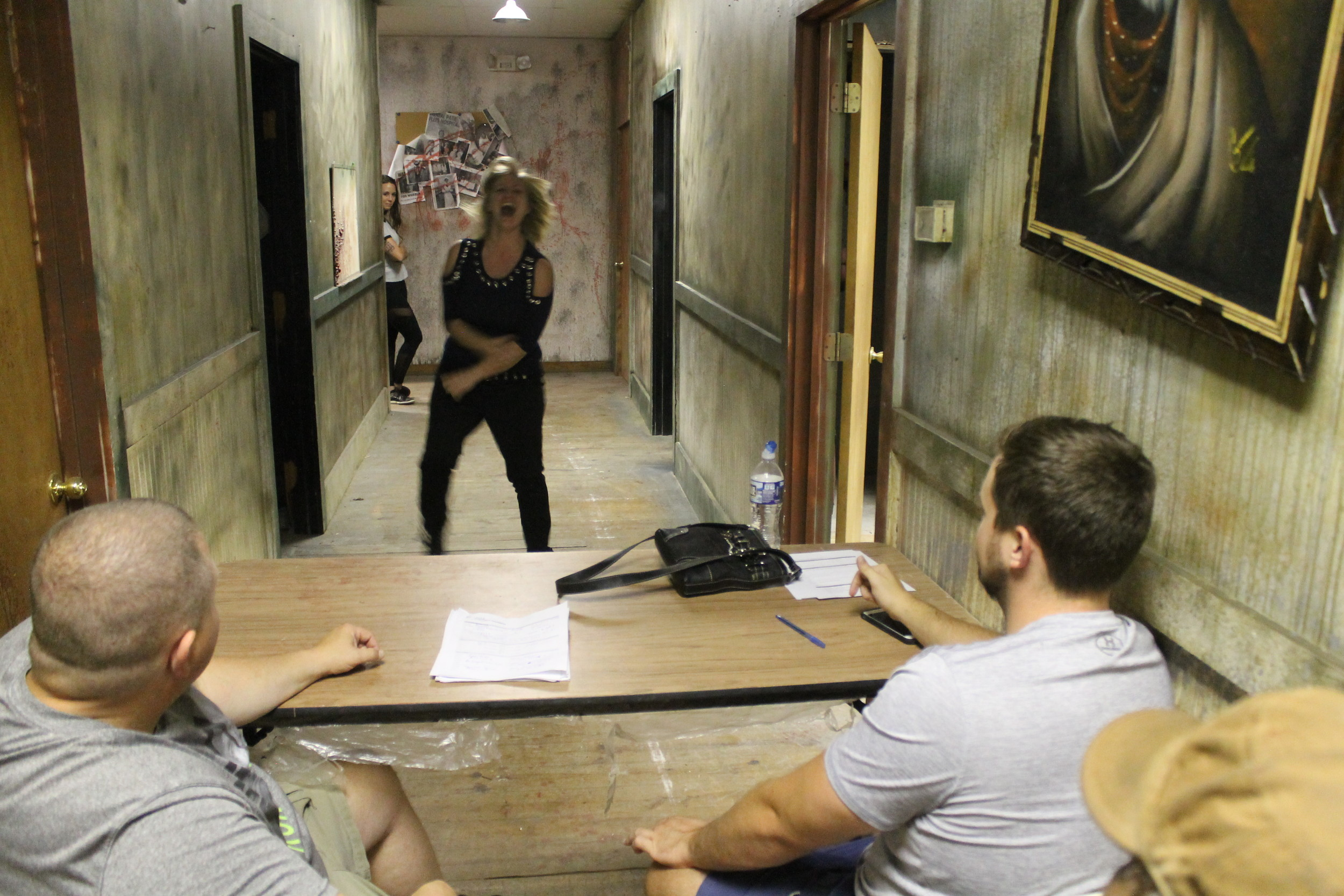 Seth Woodruff, right, and his dad, Rob Woodruff, left, watch Amanda Reynolds of Loxley audition to be a cast member at Nightmare Chambers in Fairhope. Reynolds portrayal of an insane asylum patient at the haunted house last year was so convincing that a visitor asked the staff to check on her.