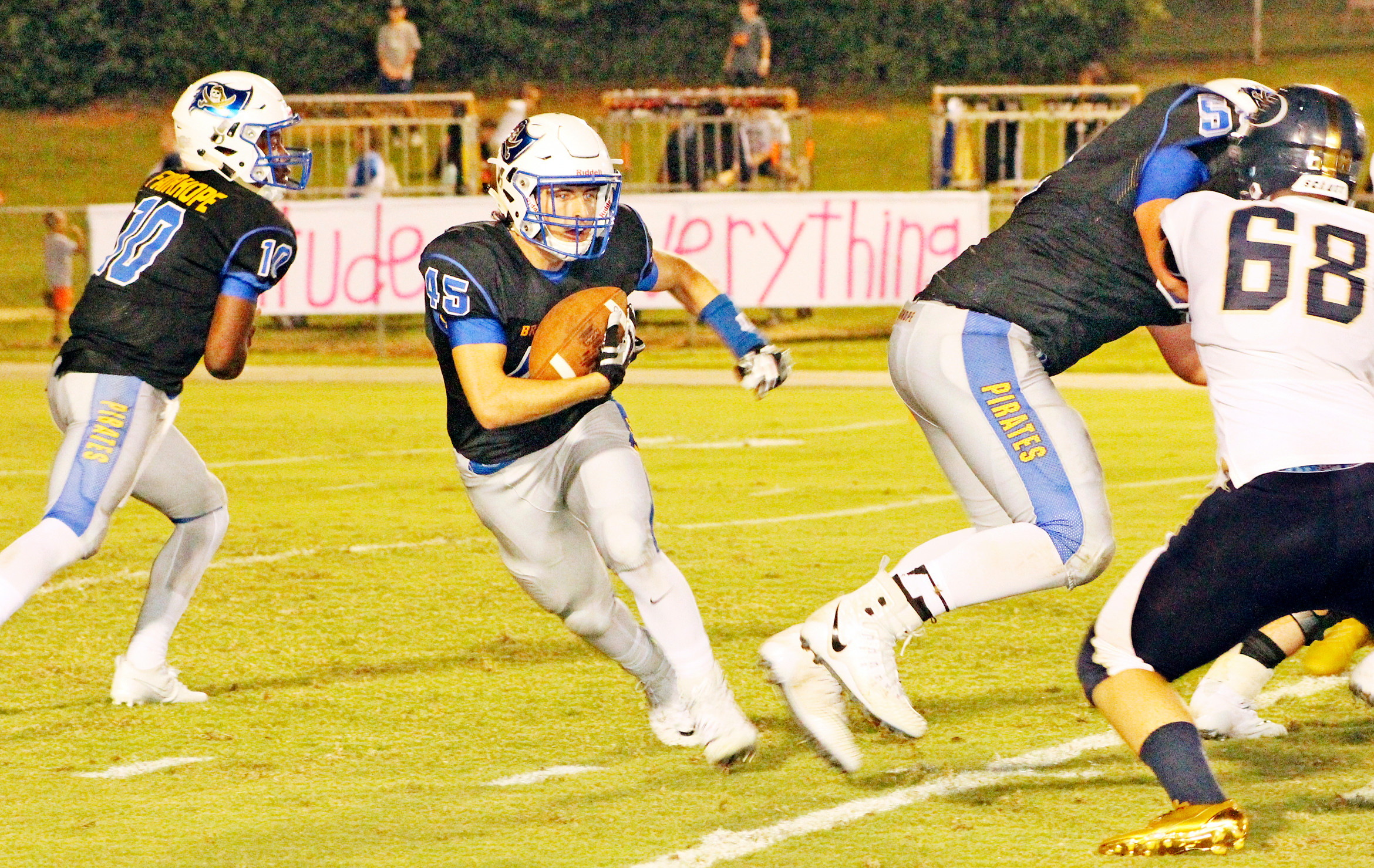 Michael Colclasure takes the hand off as Jackson DeTombe (68) defends for the Lions.