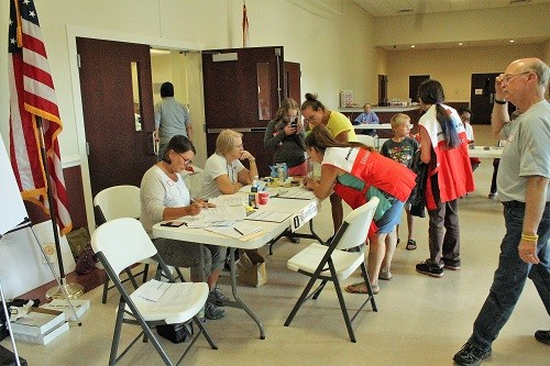 Volunteers from the American Red Cross sign in evacuees at the Baldwin County Coliseum on Sunday.