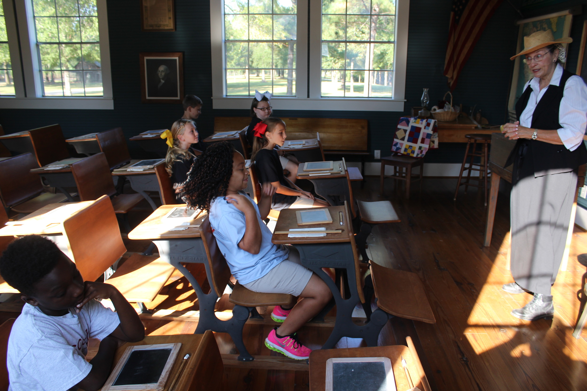 Volunteer Harriet Outlaw, known as Teacher, helps instruct her students in how school was taught in the Little Red Schoolhouse back in 1919.