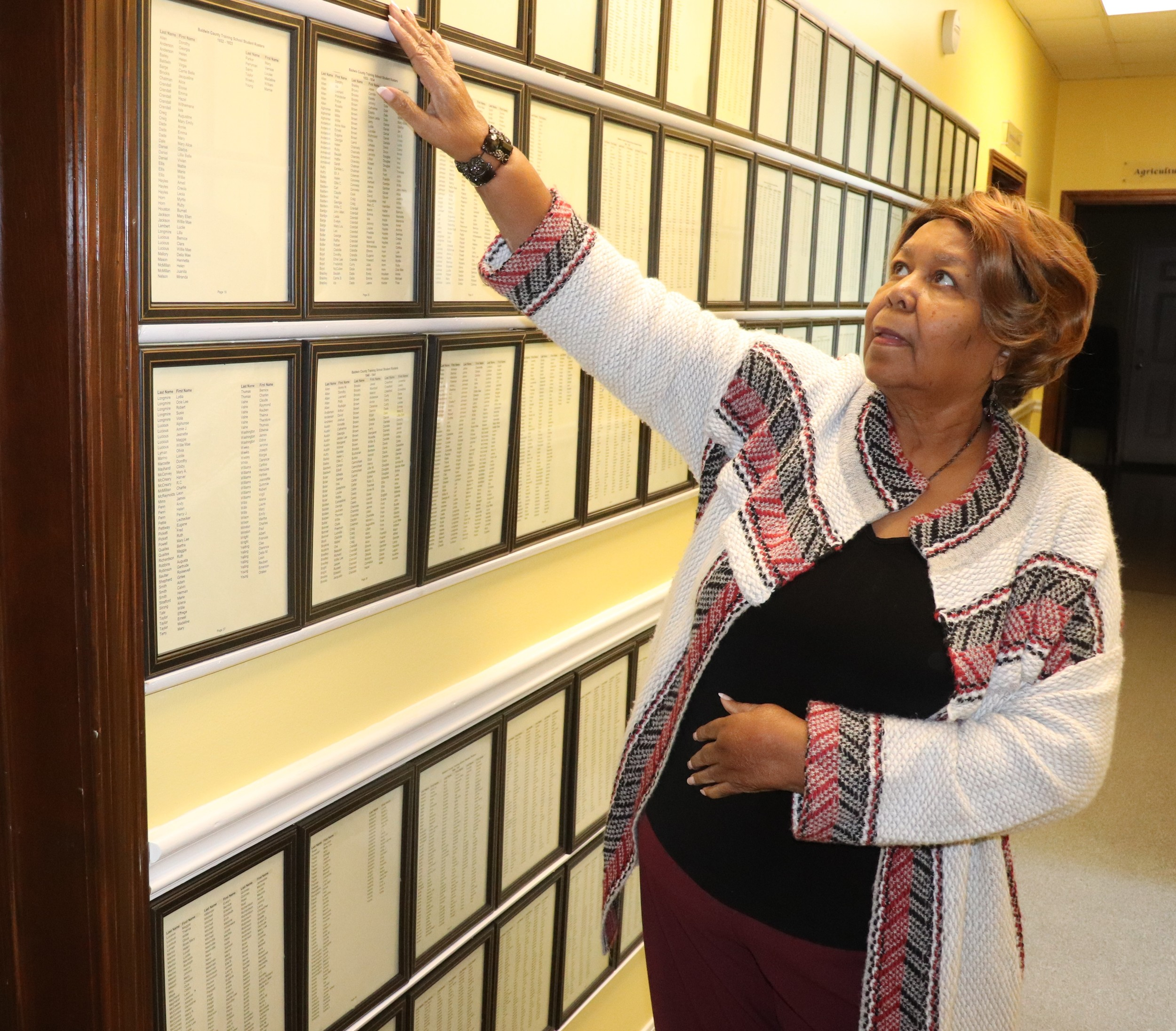Gartrell Agee looks over the names of every student who attended the Baldwin County Training School. Registers were kept beginning in 1918. Under years were there are few names, it means the crops were good and children skipped school to help with the harvest. In years with plentiful students, the crops failed.