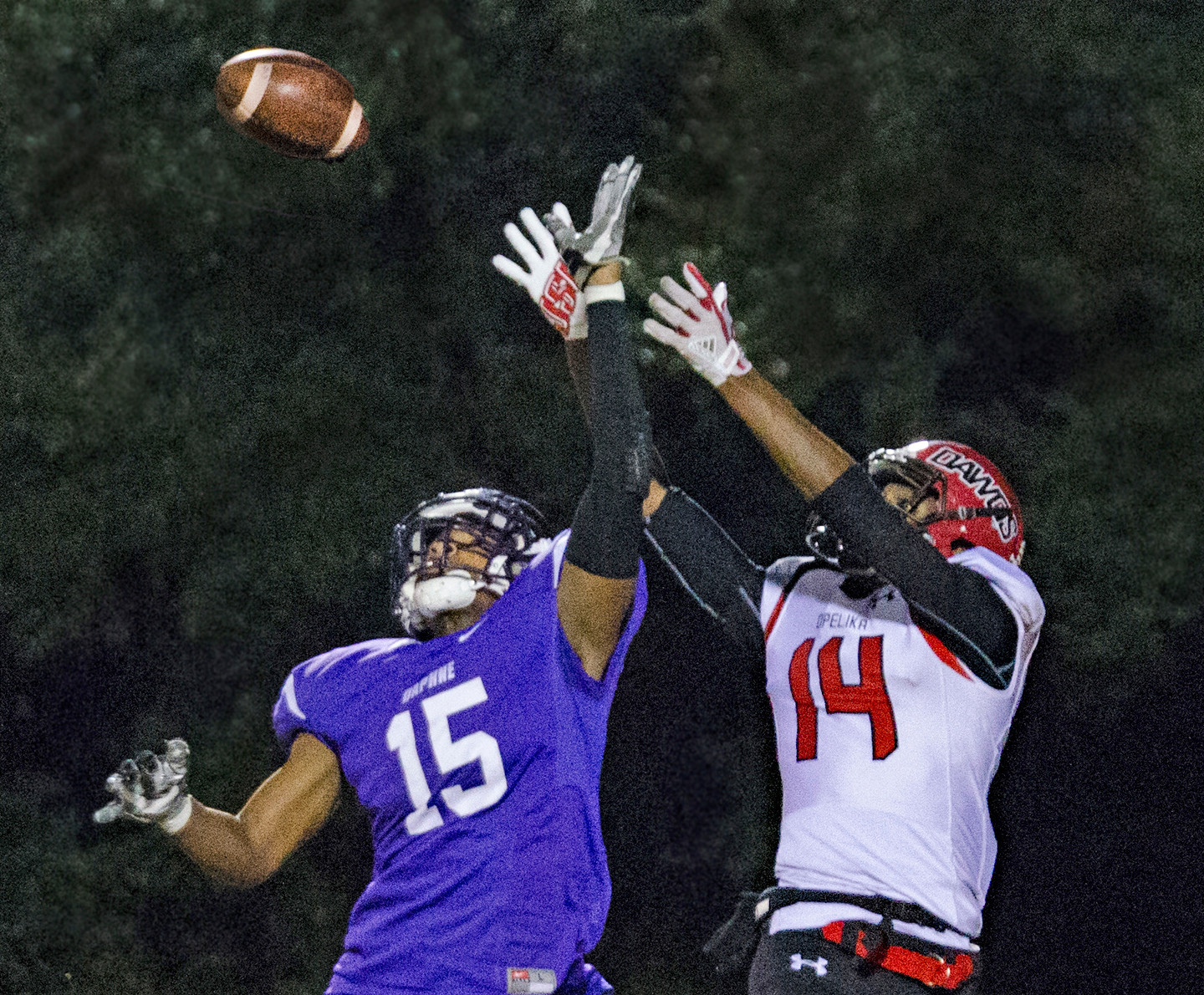 Trojan safety Hamilton Baker (15) breaks up a pass intended for Opelika's Jorden Heard (14).