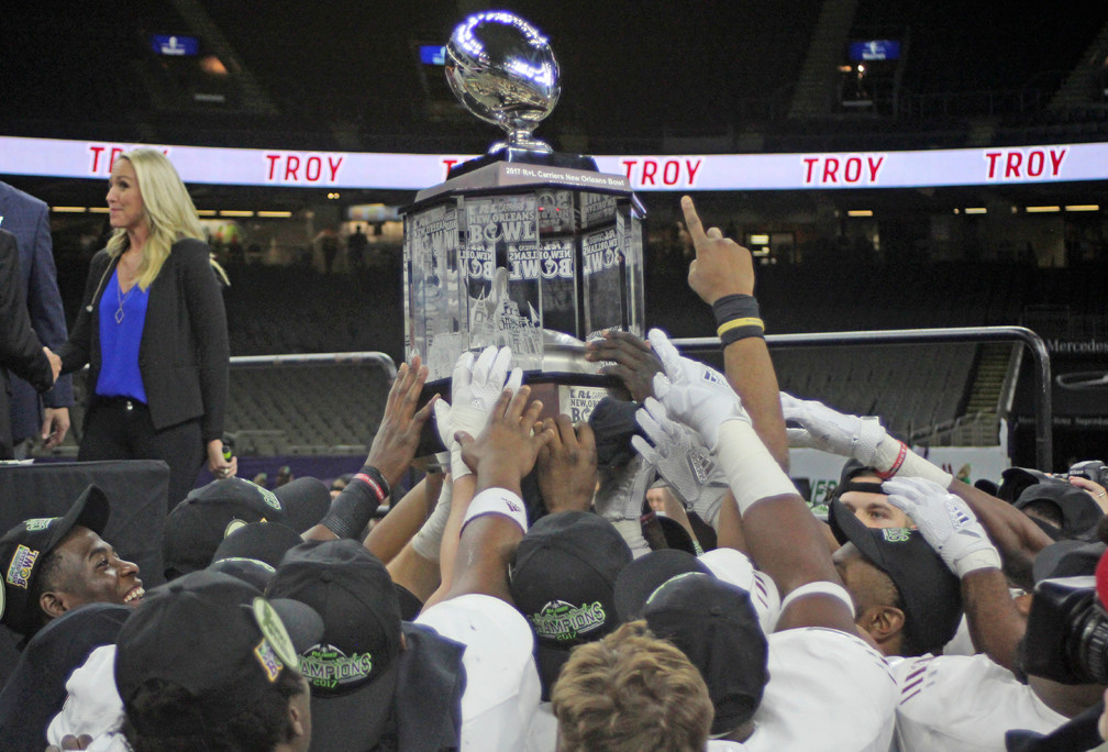 Trojans hoist the 2017 R+L Carriers New Orleans Bowl trophy.