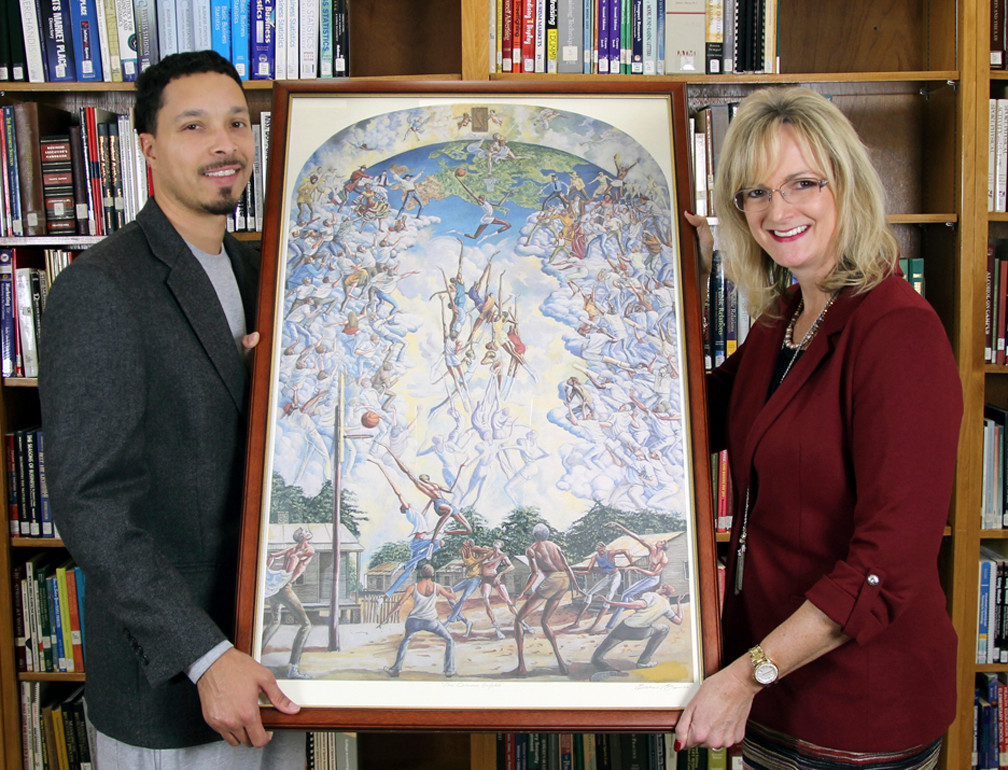 "The United States Sports Academy's American Sport Art Museum and Archives (ASAMA) has loaned six works from its collection to Stillman College for its campus art walk held in conjunction with the Dr. Martin Luther King Jr. holiday. The art walk is Saturday, 13 January 2018, from noon to 3 p.m. in Stillman's Education Building Hall. Shown with ""The Dream Unfolds"" by the late Ernie Barnes, ASAMA Sport Artist of the Year in 1984 and 2004, are Kyris Brown, left, Stillman director of international affairs and recruiting, and Holly McLellan, dean of administration and finance at the Academy."