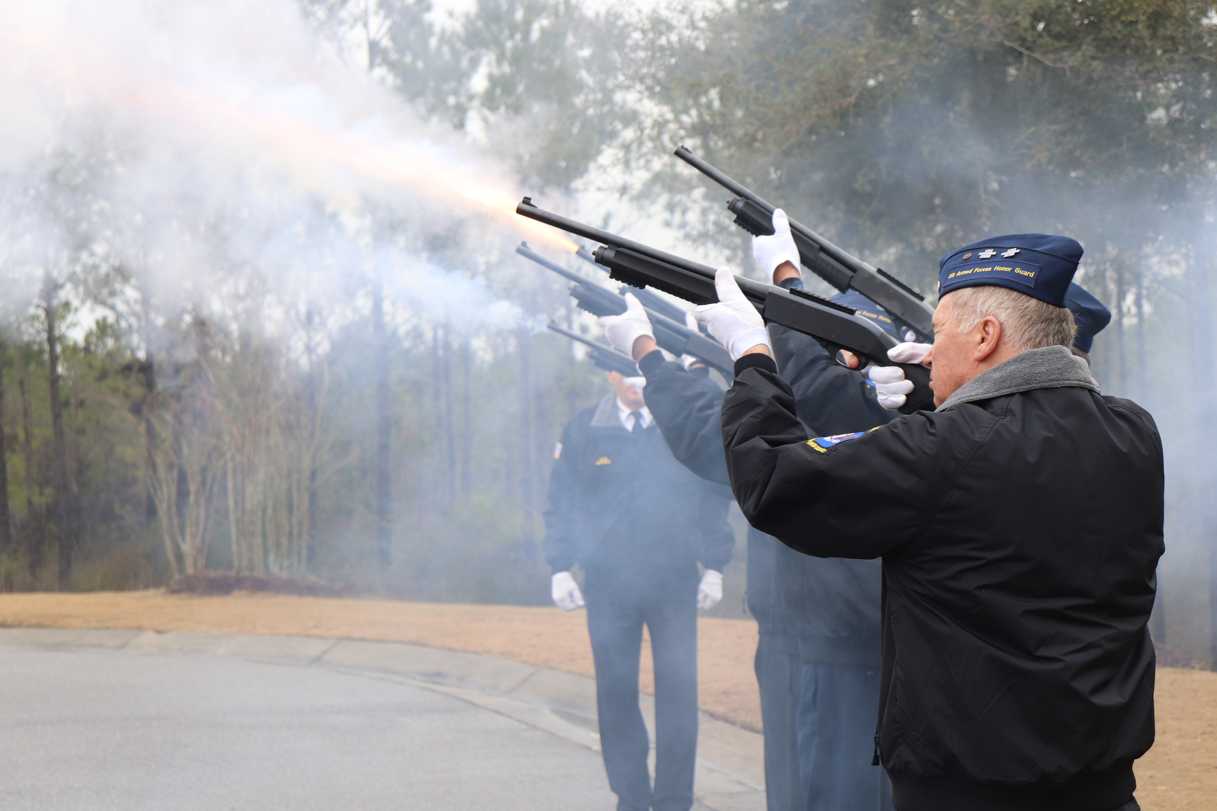 Members of the Central Baldwin County Armed Forces Honor Guard fire the first of three rounds of rifle fire during services for a veteran at the Alabama State Veterans Memorial Cemetery in Spanish Fort.