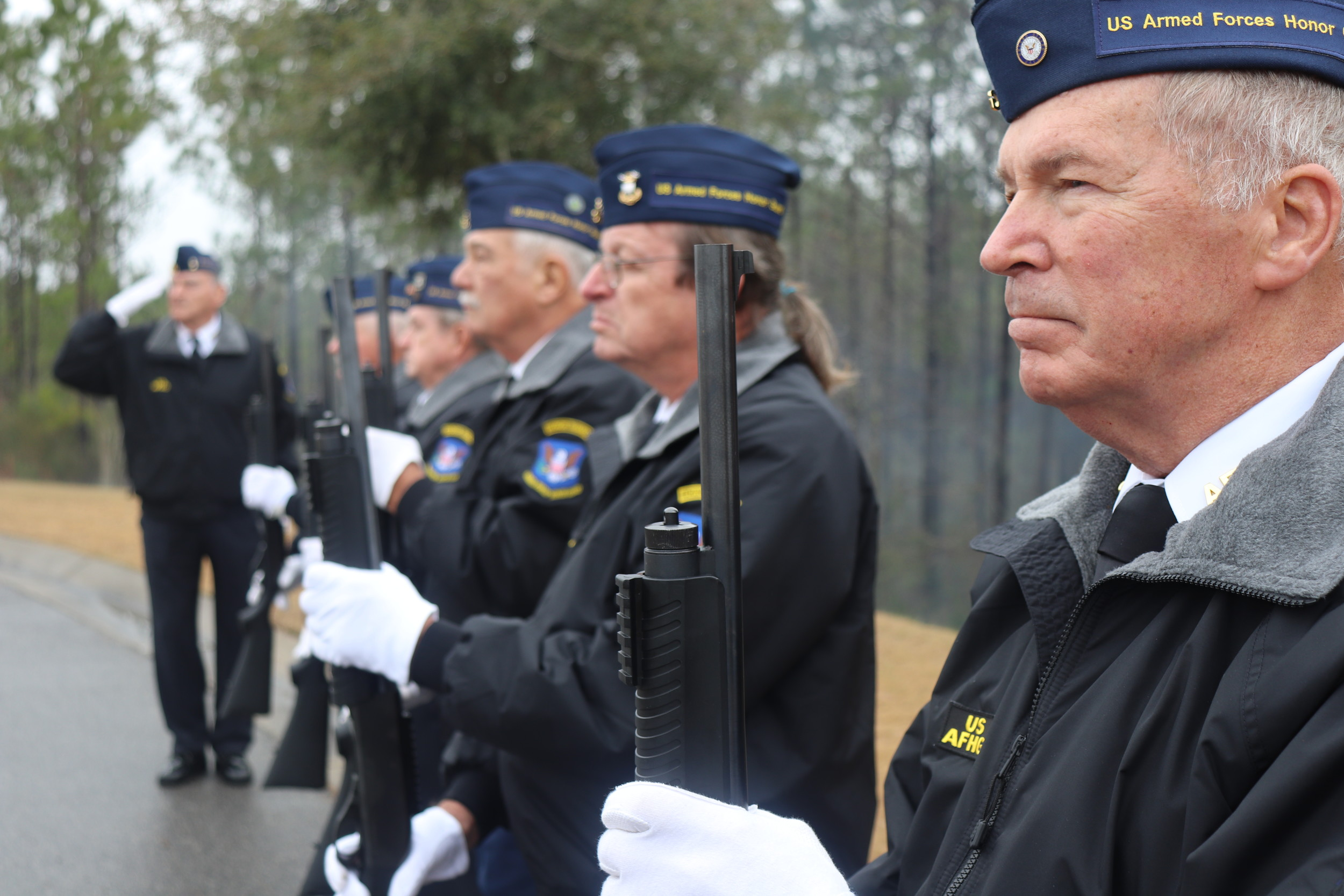 Members of the Central Baldwin County Armed Forces Honor Guard stand at the ready before the start of a veteran's funeral at the Alabama State Veterans Memorial Cemetery in Spanish Fort.