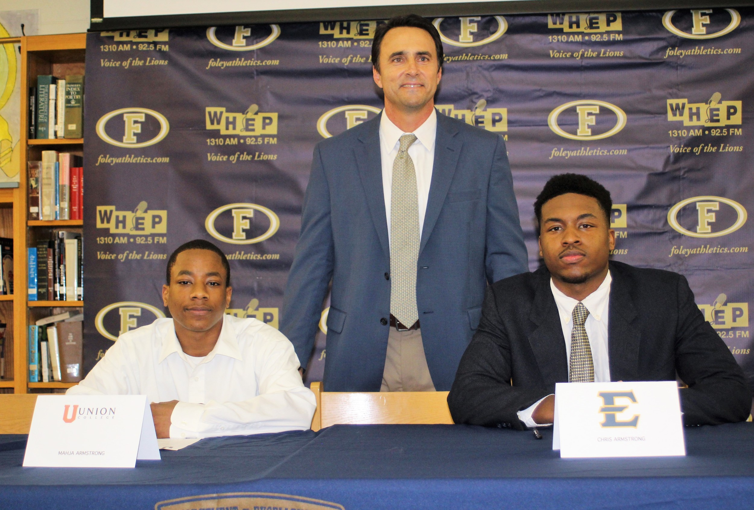 Signing day at Foley High. From left, Mahja Armstrong, FHS head coach Tad Niblett and Chris Armstrong.