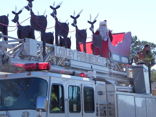 Santa rides on top of Loxley Fire Department's ladder truck during the annual Loxley Christmas Parade.