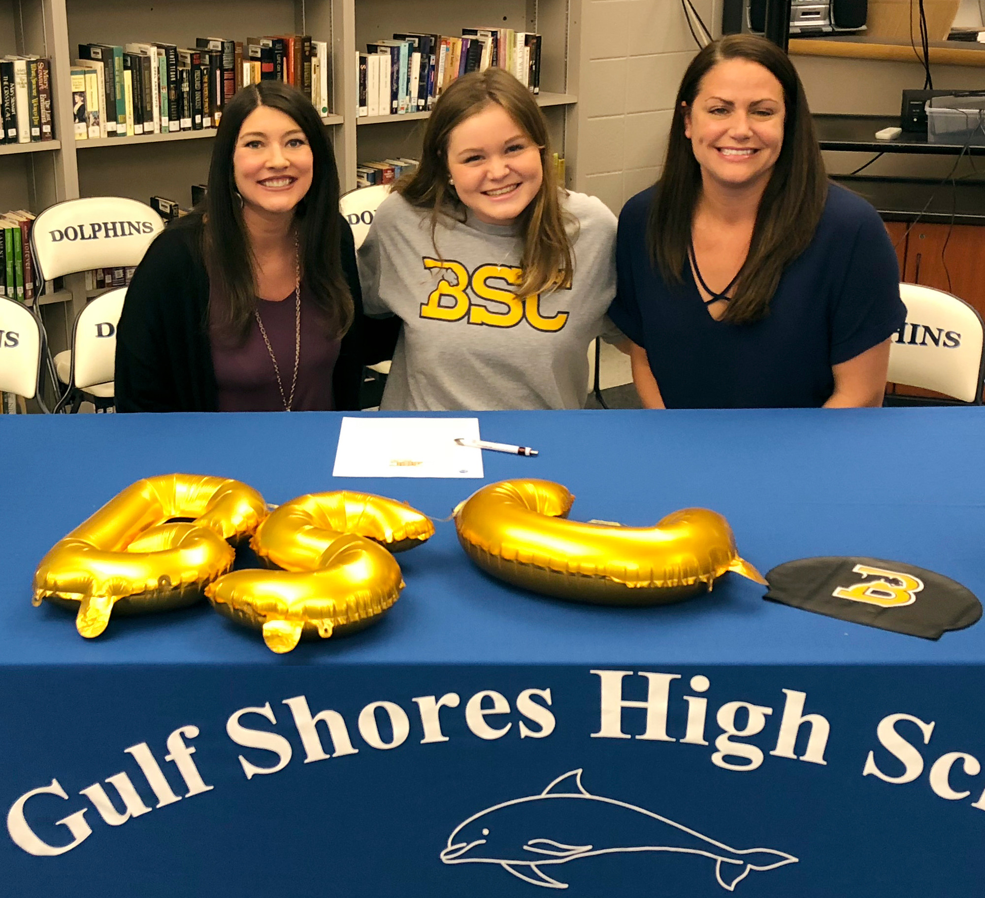 Swim coaches Tanya Farrow, left, and Brooke Hopkins with Annalane Lee on signing day.
