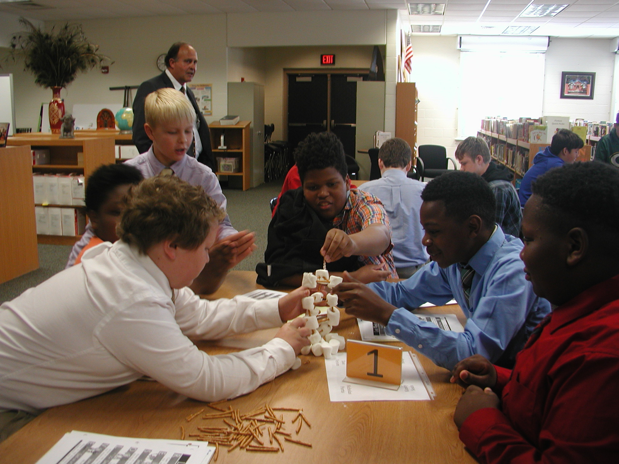 Sponsor, Anthony Roley, observes the boys constructing their marshmallow and pretzel towers.